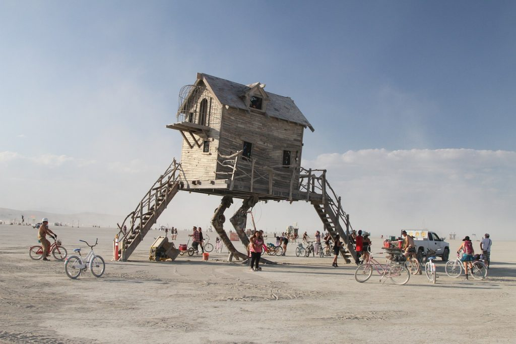 burning man sculpture house with legs in middle of desert in black rock city