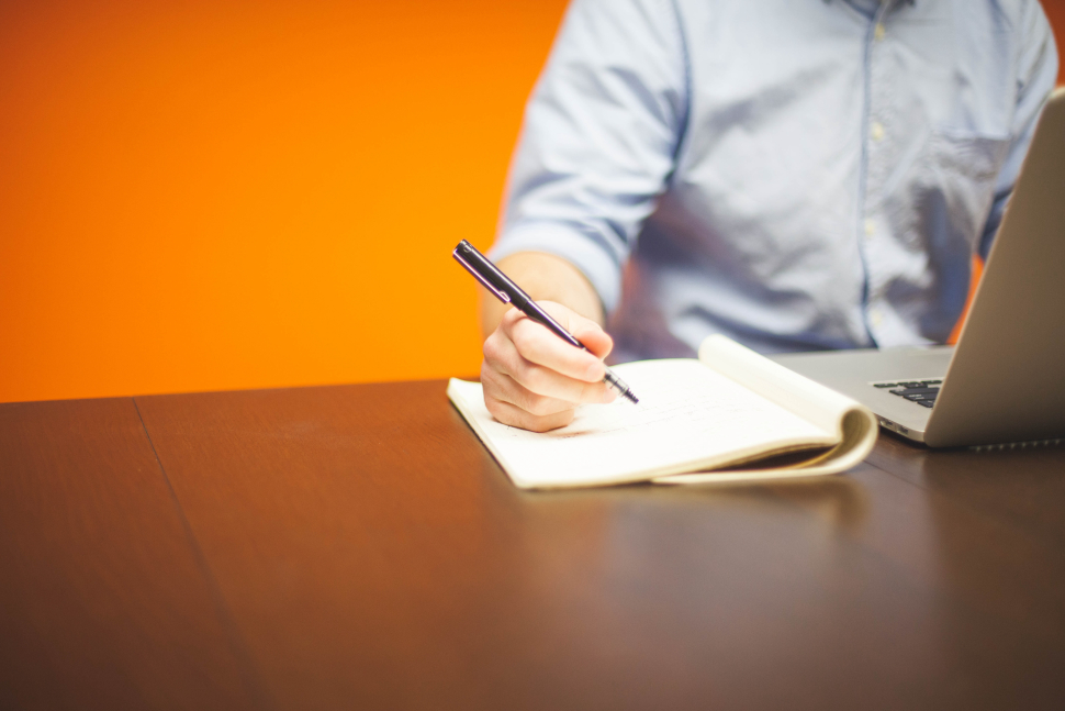 person setting goals sitting at table with laptop and notebook