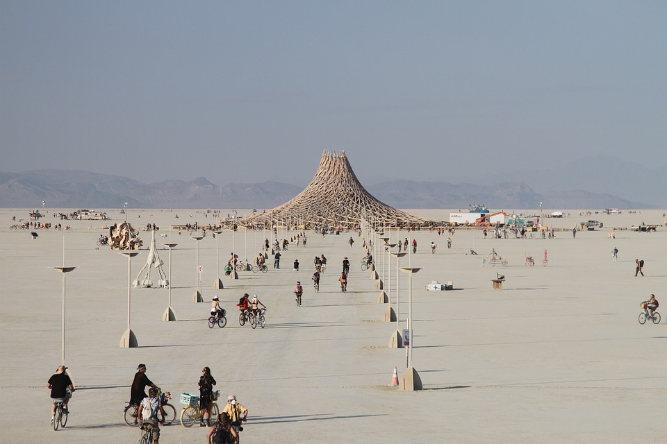 burning man artwork of volcano made out of wood with people looking on