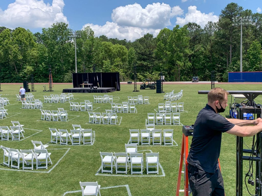 setting up pa system at outdoor high school graduation