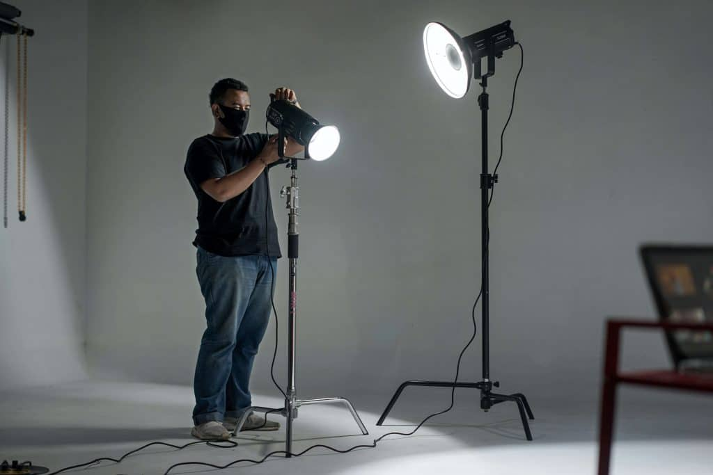 Gaffer working on a film set setting up lights for interview