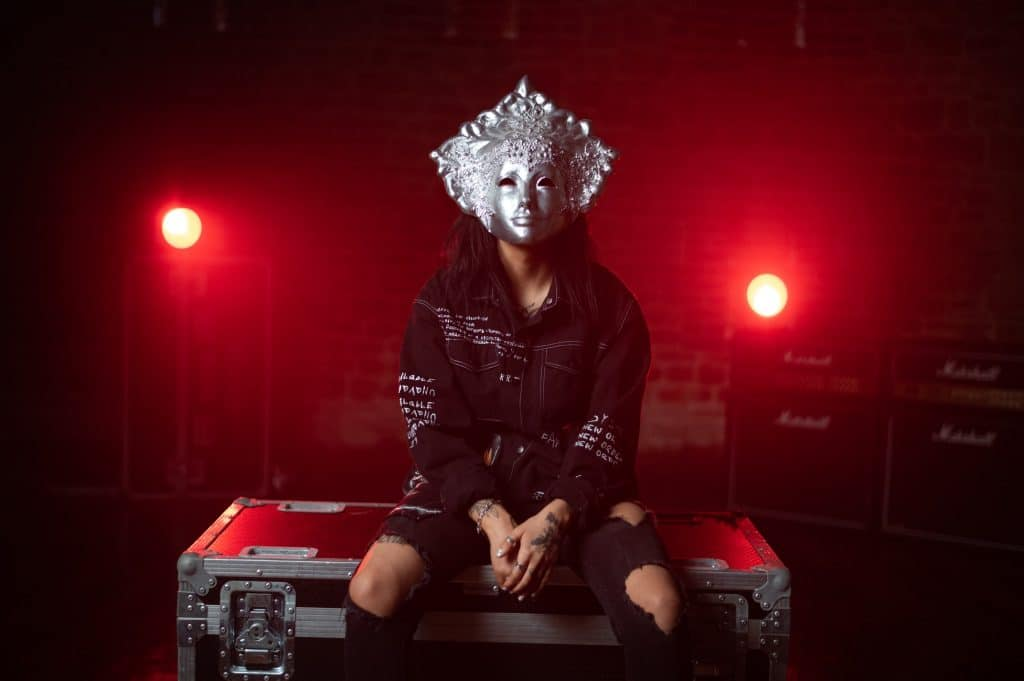 person sitting on road cases wearing a mask with red backlights shining