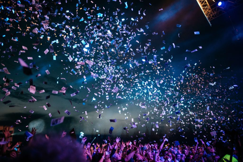 confetti at a live night event with blue and purple lights